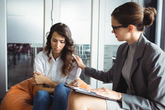 Counselor consoling unhappy woman. Counselor consoling unhappy women during therapy stock image