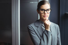 Counselor in glasses with hand on chin. At office royalty free stock photography