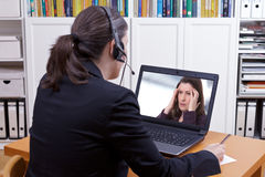 Counselor headset online call patient. Woman with headset in front of her laptop writing something on a paper while making a live video call with a patient or stock photography