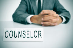 Counselor. A man wearing a suit sitting in a desk with a desktop nameplate in front of him with the word counselor royalty free stock photos