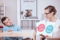 Counselor teaching autistic kid. Counselor with posters of red and blue icons teaching autistic kid of good and bad behaviors stock images
