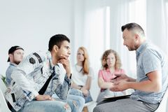 Counselor and problematic young man. Counselor telling about fails of youth and bad habits to spanish problematic young man stock photo