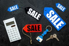 Count the benefits from the sale. Word sale on colored labels near calculator on black background top view Royalty Free Stock Images