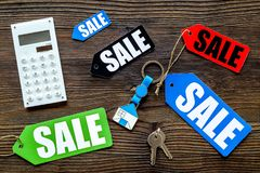 Count the benefits from the sale. Word sale on colored labels near calculator on wooden background top view Stock Photos