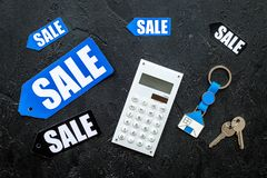 Count the benefits from the sale. Word sale on label near calculator on black background top view Stock Image