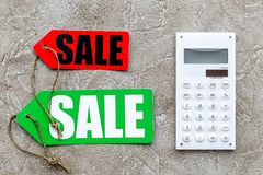 Count the benefits from the sale. Word sale on label near calculator on light stone background top view Stock Images