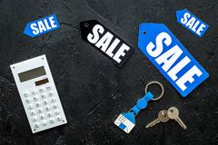 Count the benefits from the sale. Word sale on colorful labels near calculator on black stone background top view Royalty Free Stock Images