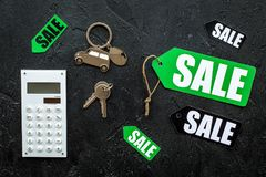 Count the benefits from the sale. Word sale on label near calculator on black background top view Royalty Free Stock Images