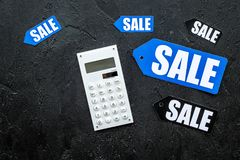 Count the benefits from the sale. Word sale on label near calculator on black background top view copyspace Royalty Free Stock Photography