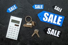 Count the benefits from the sale. Word sale on label near calculator on black background top view Stock Images