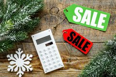 Count the benefits from the winter sale. Word sale on colored labels near calculator and spruce branch on wooden Stock Image