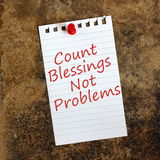 Count Blessings Not Problems. The phrase Count Blessings, Not Problems on a piece of lined paper pinned to a grunge background with a red push pin royalty free stock photography