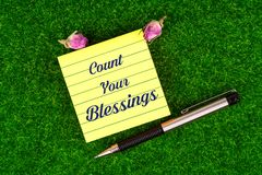 Count your blessings. In sticky note with pen and dried rose buds on grass royalty free stock image