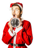 Countdown to christmas time coming soon. Shocked man in santa suit holding clock with a minute to spare till midnight. Countdown to christmas time coming soon stock images