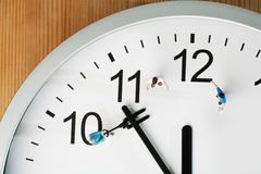 Countdown To Midnight And New Year. A team of miniature toy figurines tries to push the minute hand to midnight, closeup on a portion of a clock face stock photography