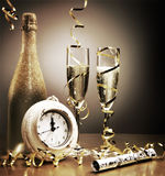 Countdown to midnight on New Years Eve. Stylish gold still life depicting the countdown to midnight on New Years Eve with a clock, party cracker, streamers and stock photography