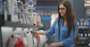 Counter of electronics store. Young beautiful brunette woman holding an electric kettle in her hands, studying the price. Tags, characteristics and design of stock footage
