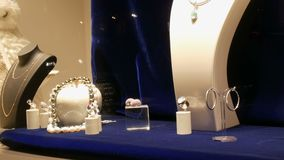 Counter with expensive luxury jewelry made of gold, silver, pearls in the window of jewelry store stock video footage