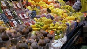 Counter with Fruits at a Market in La Boqueria. Barcelona. Spain. Peach, grapes, kiwi, mango and other exotic fruits on display on the showcase at Mercat de stock footage