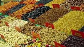 On a counter of the market dried fruits and nuts lie stock footage