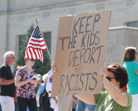 Counter Protestors with sign at a Rally to Secure Our Borders. Counter Protestors with a sign saying keep the kids deport the racists across the street from a Royalty Free Stock Image