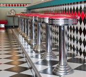 Counter Stools in a row at a 50's style diner. Counter stools in a row with checkerboard tile floor at a 1950 style diner royalty free stock image
