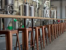 Counter top and cooper stools sitting in front of brewery tanks stock photos