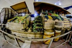 Counter which are boxes of grapes, wine bottles and wooden wine barrels in Italy stock image