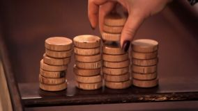 Counters for playing the Dutch billiards. The woman spreads them in a pile. Wooden counters. Counters for playing the Dutch billiards. The woman spreads them in stock footage