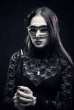 Countess of darkness. Pretty gothic girl in mask holding candle over dark background royalty free stock photos