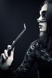 Countess of darkness. Pretty gothic girl in mask holding candle over dark background royalty free stock photo