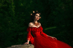 Countess in long red dress sitting with his eyes closed. Royalty Free Stock Photography