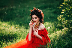 Countess in a long red dress. Is walking in a green forest full of branches, elf, Princess in vintage dress, the queen of the forest,fashionable toning creative royalty free stock images