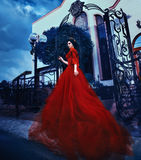 Countess in a long red dress walks near the castle. Beautiful brunette girl with long hair. She's in a vintage red dress with bare shoulders. The Queen walks stock image