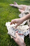 Counting 100 dollar bills, US. First person perspective of man counting hundred dollar bills while relaxing on the lawn Stock Image