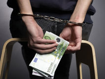 Counting. Money with handcuffs on black background Royalty Free Stock Images