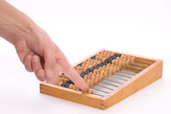 Counting by abacus. Moving bones on the counting frame by hand Royalty Free Stock Photo