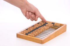 Counting by abacus. Moving bones on the counting frame by hand Royalty Free Stock Photography