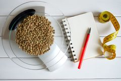 Counting calories, fat, carbohydrates and proteins in food. Lentil seeds on kitchen scales. Slim figure, fitness, weight loss, diet and proper nutrition stock photo
