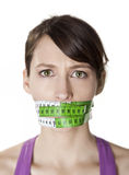 Counting calories. Portrait of a young  woman with a green measuring tape covering the mouth Stock Photo