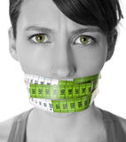 Counting calories. Portrait of a young  woman with a green measuring tape covering the mouth Stock Images