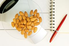 Counting calories, proteins, fats and carbohydrates in food. Almond nuts on table scales. Slim figure, diet, weight loss and proper nutrition royalty free stock photo