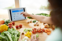 Counting calories. Woman consulting application on her digital tablet to know how many calories she consumed royalty free stock photo