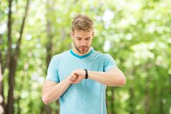 Counting calories. Wrist band gadget. Athlete check fitness tracker nature background. Athlete with bristle looks at. Pedometer gadget progress result royalty free stock image