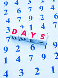 Counting the days. Text ' days ' in red uppercase letters on small white cubes  placed upon an array of numbers in blue  making the concept of counting the days Stock Photography