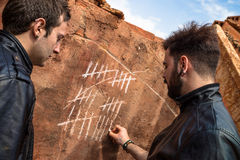 Counting days. Two guys couning days with chalk markings on a wall royalty free stock photos