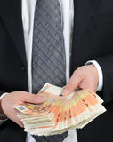 Counting euros. Business dressed man counts 50-euro banknotes Royalty Free Stock Photos