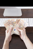 Counting Euros banknotes on computer Royalty Free Stock Photos