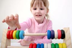 Counting girl. Little girl make some calculation with toy coloured wooden abacus Royalty Free Stock Photos