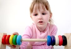 Counting girl. Little girl make some calculation with toy coloured wooden abacus Royalty Free Stock Photo